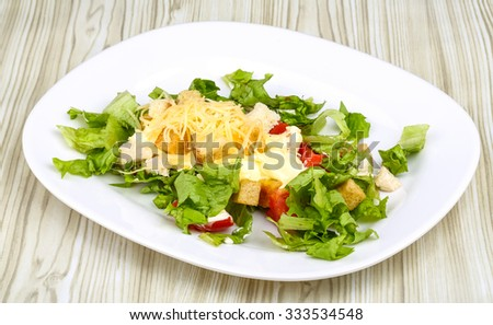 Caesar salad with chicken on the wood background - stock photo