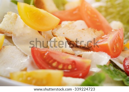 caesar salad with chiken fillet and different color tomatoes, close up