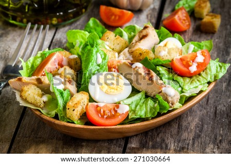 Caesar salad with croutons, quail eggs, cherry tomatoes and grilled chicken in wooden plate on dark rustic table - stock photo