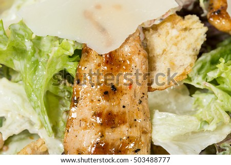 Caesar salad with grilled chicken and parmesan. Macro. Photo can be used as a whole background.