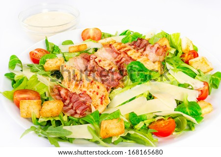 Caesar Salad with grilled chicken and sauce on white plate - stock photo