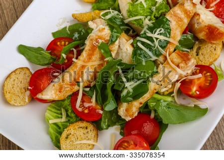 Caesar salad with grilled chicken breast on the wood background