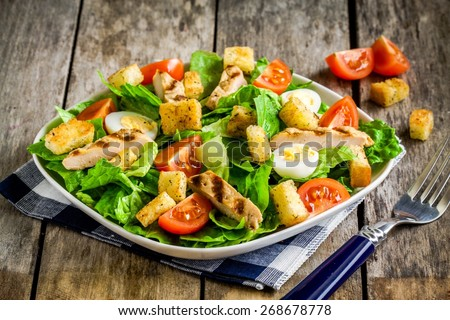 Caesar salad with grilled chicken, croutons, quail eggs and cherry tomatoes  on wooden rustic table - stock photo