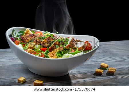 Caesar salad with hot chicken and fresh vegetables - stock photo