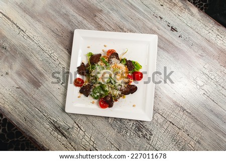 Caesar salad with meat and tomatoes on wood table - stock photo