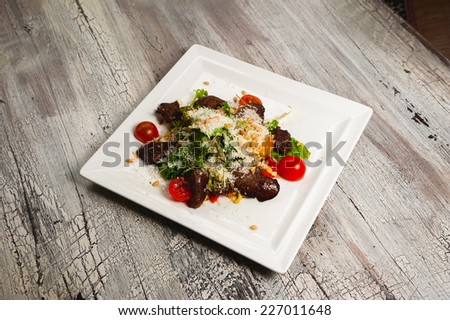 Caesar salad with meat, tomatoes and grated parmesan - stock photo