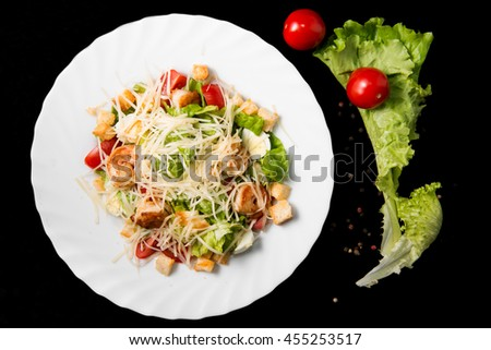 Caesar salad with prawns, cherry tomato and cheese on white plate