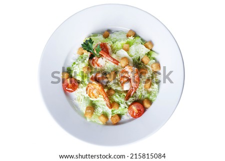 Caesar salad with shrimp on a plate on a white background - stock photo