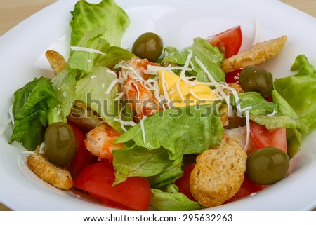 Caesar salad with tiger prawn on the wood background