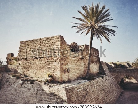 Caesarea Maritima National Park, Ancient Roman city shown at sunset time. Ruins of Crusader fortress. Filtered image, vintage effect applied - stock photo