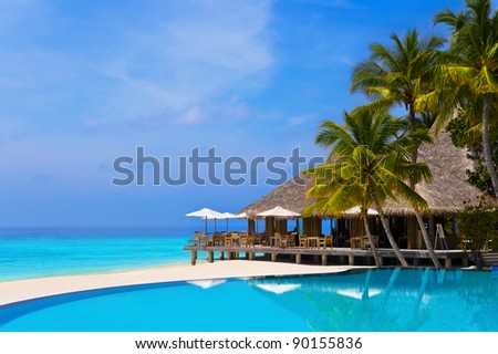 Cafe and pool on a tropical beach - travel background - stock photo