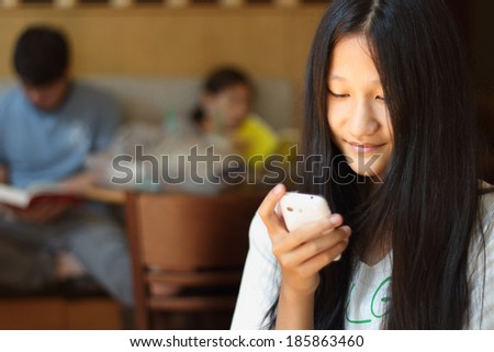 Cafe city lifestyle woman on phone drinking coffee texting text message on smartphone app sitting indoor in trendy urban cafe. Cool young modern mixed race Asian Caucasian female model in her 15s.  - stock photo