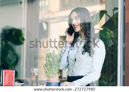 Cafe city lifestyle. Young woman sitting indoor in trendy urban cafe talking with her mobile phone. Cool young modern caucasian female model in her 20s - stock photo