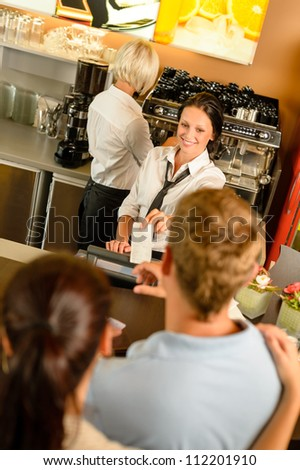 Cafe employee woman giving man bill receipt woman customer bar - stock photo