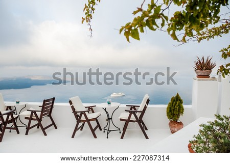 Cafe on the terrace with a beautiful sea view. Foggy morning. White architecture on Santorini island, Greece - stock photo