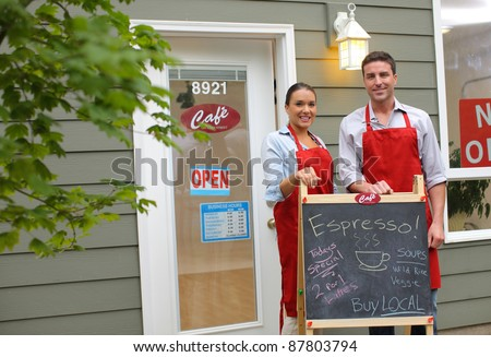 Cafe owners in front of shop - stock photo