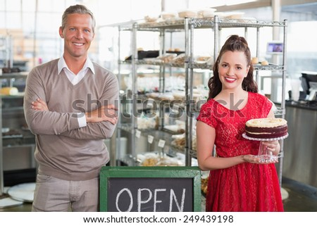 Cafe owners smiling at the camera at the cafe - stock photo
