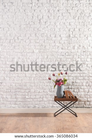 cafe table with brick wall and vase of flower - stock photo