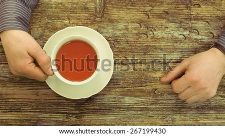 cafe table wooden male hands holding  tea cup tint top view - stock photo