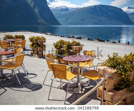 cafe. tables and chairs on the shore of the fjord in Norway - stock photo