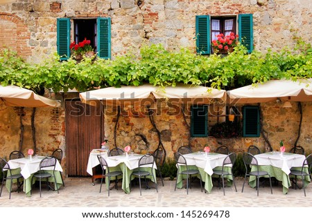 Cafe tables and chairs outside a quaint stone building in Tuscany, Italy - stock photo