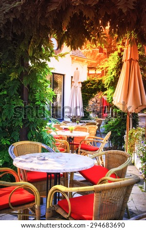 Cafe terrace in small European city on sunny summer day - stock photo