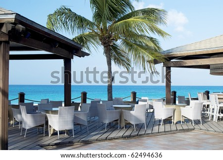 Cafe with white chairs  on the beach,  obn caribian ocean and sunny  sky with palm tree. - stock photo