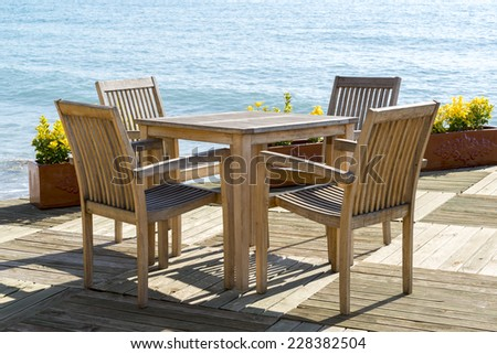 Cafe with wooden tables and chairs at the seaside - stock photo