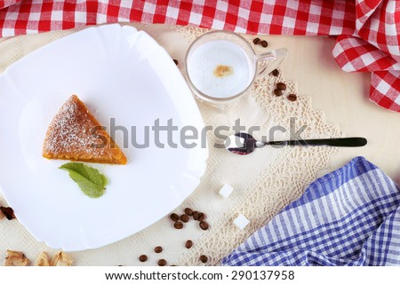 Cafeteria, table in a cafe, restaurant. Dessert on the plate and a Cup of latte. A Cup of cappuccino, a piece of cake, the sugar cubes, spoon and coffee beans on the table. Good morning. Coffee time. - stock photo