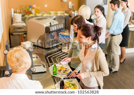 Cafeteria woman pay at cashier hold serving tray fresh food - stock photo
