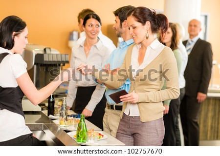 Cafeteria woman pay by credit card cashier food on serving tray - stock photo