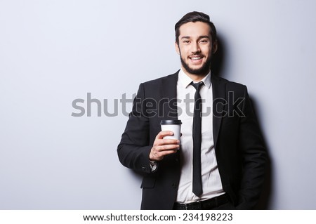 Caffeine for charging before working. Portrait of confident young man in formalwear looking at camera and holding cup of coffee while standing against grey background