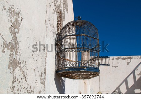 Cage on the roof and blue sky Empty stylish bird cage hanging on the old wall. Bright blue sky. - stock photo