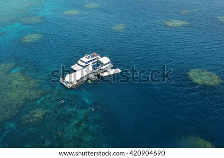 CAIRNS, AUS - APR 15 2016: Aerial view of reef with all-weather marine diving platform and boats at the Great Barrier Reef world's largest coral reef system, near Cairns Queensland Australia. - stock photo