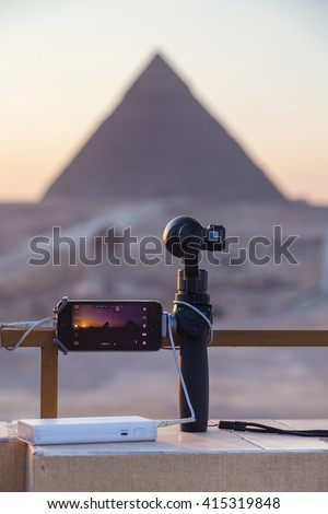 CAIRO, EGYPT - FEBRUARY 2, 2016: iPhone on Osmo device and battery pack set up to record timelapse of The Great Pyramid of Giza at sunset. - stock photo