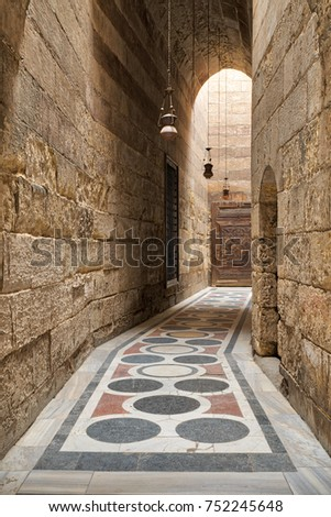 Cairo, Egypt - March 18, 2017: Arched corridor leading to the courtyard of Sultan Barquq mosque with stone bricks wall, ornate colored marble floor and wooden door, Old Cairo, Egypt