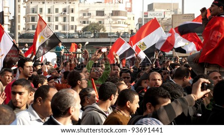 CAIRO – JAN 25: Groups of Egyptians walk in a giant march across down town area during first anniversary of Egypt's uprising calling for further political reforms in Cairo, Egypt on January 25, 2012 - stock photo