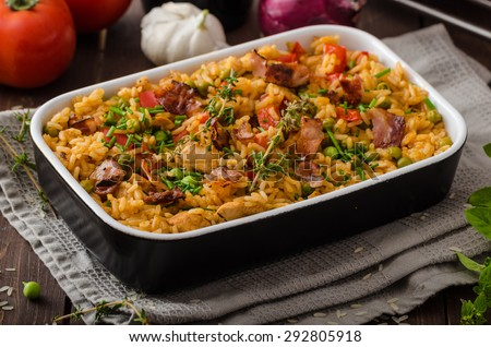 Cajun chicken with rice,  full of flavor and hot spices with fresh vegetable bio peas - stock photo
