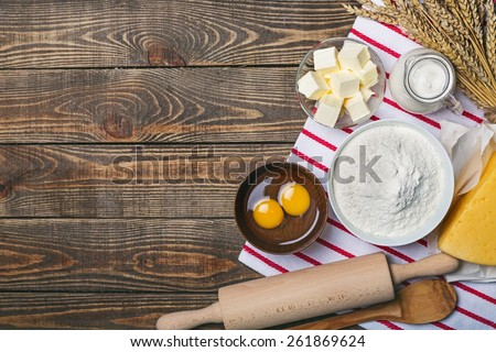 Cake. Baking cake in rural kitchen - dough recipe ingredients (eggs, flour, milk, butter, sugar) and rolling pin on vintage wood table from above. Rustic background with free text space. - stock photo