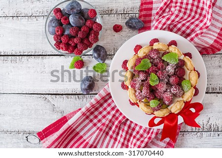 "Cake ""Charlotte "" with raspberries and plums. Top view - stock photo"