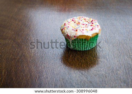 Cake Cupcake Food Dessert Single Small Cupcake with white icing and hundreds and thousands sprinkles on dark wooden background - stock photo