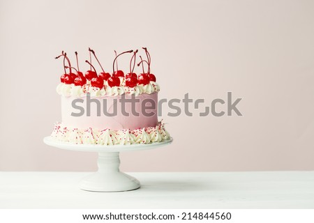 Cake decorated with frosting and maraschino cherries  - stock photo