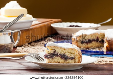 cake filled with jam and icing sugar on a dish