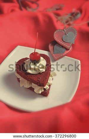 cake in heart shape on red fabric - stock photo