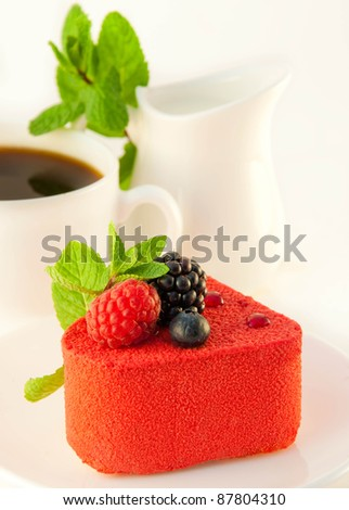 Cake in the form of heart with a blackberry, a raspberry and mint, a cup of coffee - stock photo