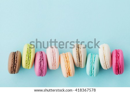 Cake macaron or macaroon on turquoise background from above, colorful almond cookies, pastel colors, vintage card, top view