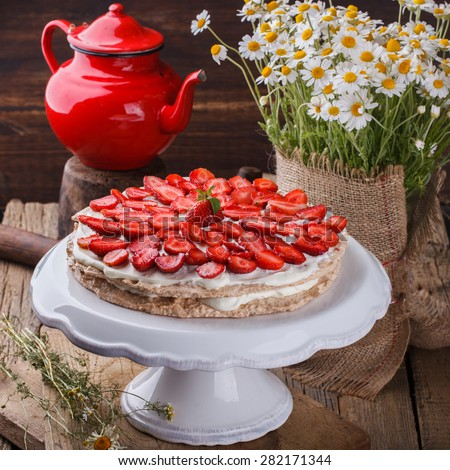 Cake meringue cakes with strawberries .Bouquet of daisies in a vase.selective focus - stock photo