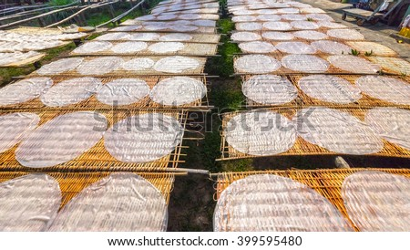 Cake noodles drying on field with round cake noodles drying on bamboo blisters dry just put a lot of goods then cut into strands, bring in food processing areas most delicious noodles Can Tho, Vietnam - stock photo