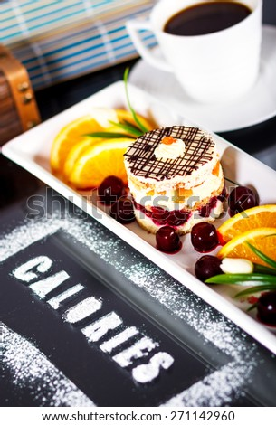 Cake on a white plate with fresh fruit with word calories written on the table. - stock photo