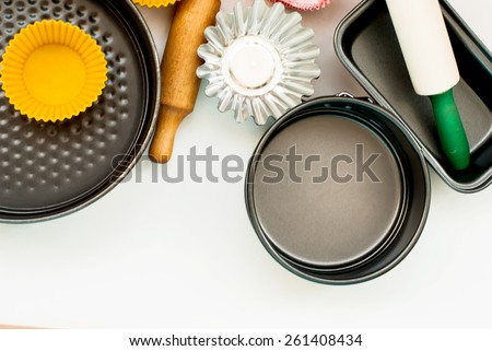 Cake pans and round metal bakeware, wooden rolling pin on a wooden background - stock photo